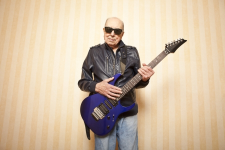 cool fashion elder man with electric guitar photo