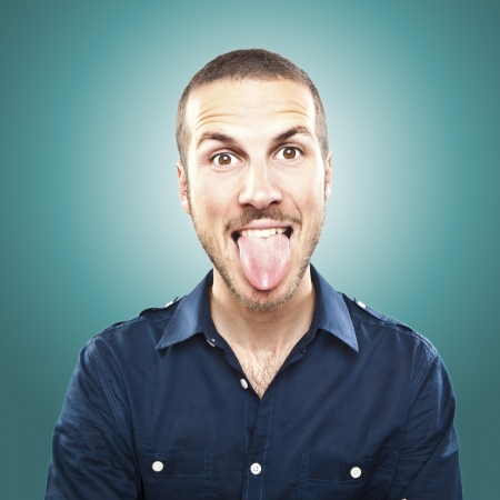 facial expression: portrait of a young beautiful man showing tongue, face expression