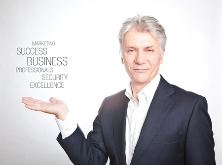 Happy senior businessman with hand gesture showing copyspace on white background