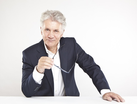 Successful mature businessman looking at camera  at work in office photo