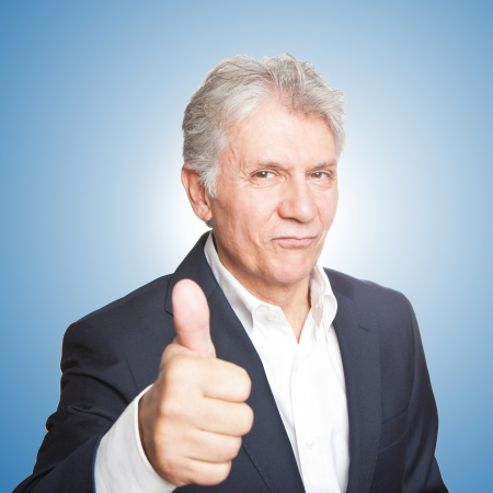 Portrait of confident mature businessman with  thumbs up on whit photo