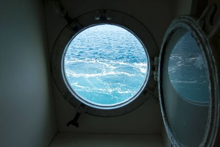 Boat porthole with ocean view photo