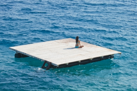 raft: young woman relaxing  on a wooden raft in the sea