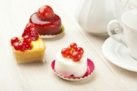 fruit pastry little cake with tea cup on white wooden table photo