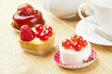 fruit pastry little cake with tea cup on  wooden table photo