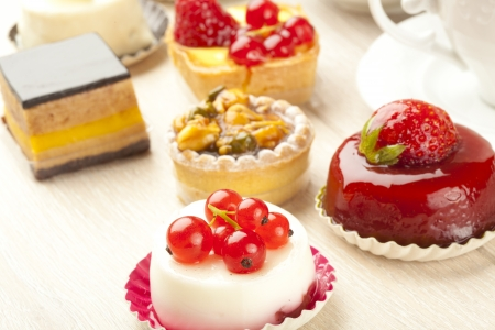 Different sort of beautiful pastry, small colorful sweet cakes photo