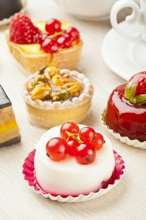 Different sort of beautiful pastry, small colorful sweet cakes Stock Photo
