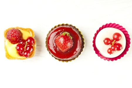 sweet pastries: small beautiful red fruit pastry on wooden table