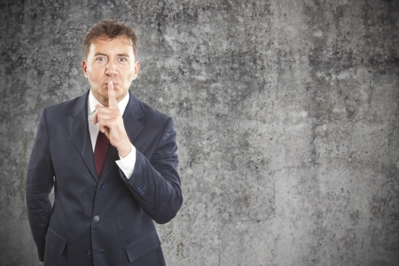 businessman making silence gesture on cement background photo