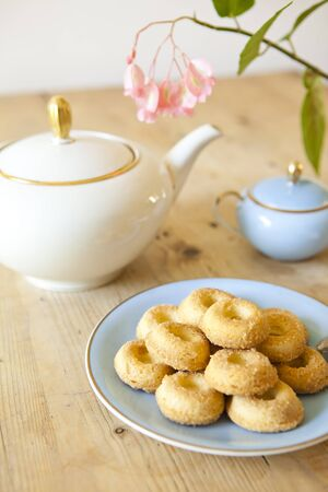 a plate of biscuits, a tea pot and a flower on wooden table photo