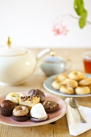 plates of pastries and biscuits and tea pot on wooden table Stock Photo - 15528620