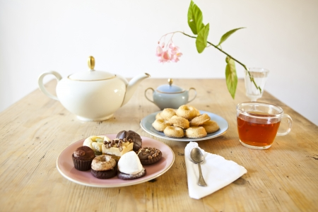 little table: plates of pastries and biscuits and tea pot on wooden table Stock Photo