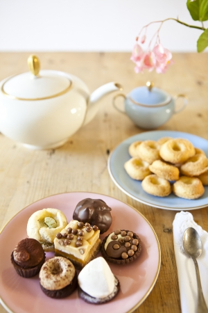 plates of pastries and biscuits and tea pot on wooden table Stock Photo - 15528648