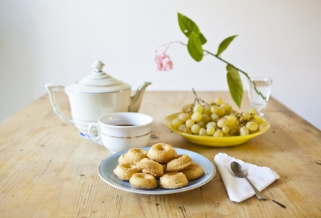 plates of pastries and biscuits and tea pot on wooden table photo