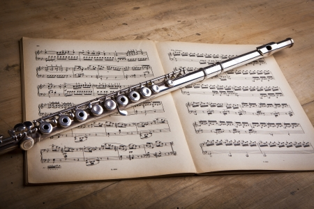 Silver flute on an ancient music score background Stockfoto