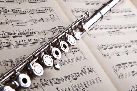 partition musique: Flûte d'argent sur un fond score de musique ancienne