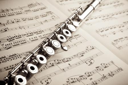 Silver flute on an ancient music score background Standard-Bild