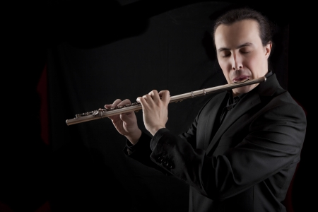 professional flutist musician playing flute on black background photo