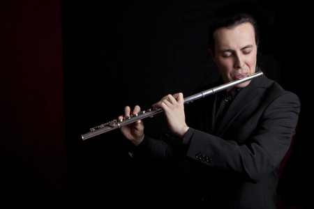 silver flute: professional flutist musician playing flute on black background Stock Photo