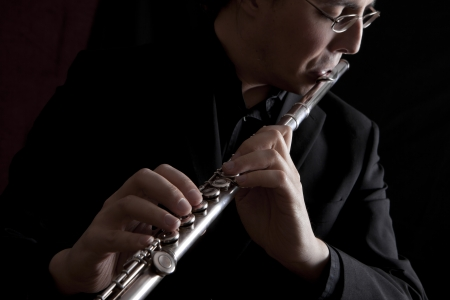 flute: professional flutist musician playing flute on black background Stock Photo