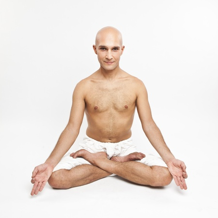 meditation man: young man practicing yoga on white background, meditating in lotus position.
