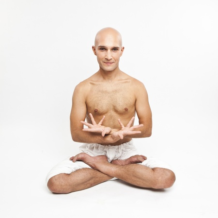 young man practicing yoga on white background, meditating in lotus position. photo
