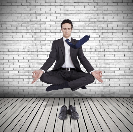 young businessman levitating in yoga position, meditation Stock Photo