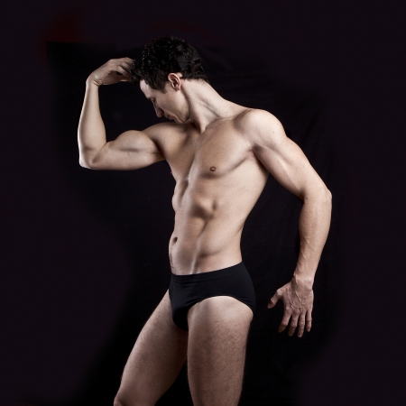 man underwear: Handsome muscular man on black background Stock Photo