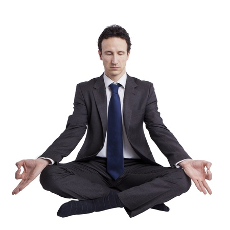 young businessman meditating in yoga lotus pose on white background photo