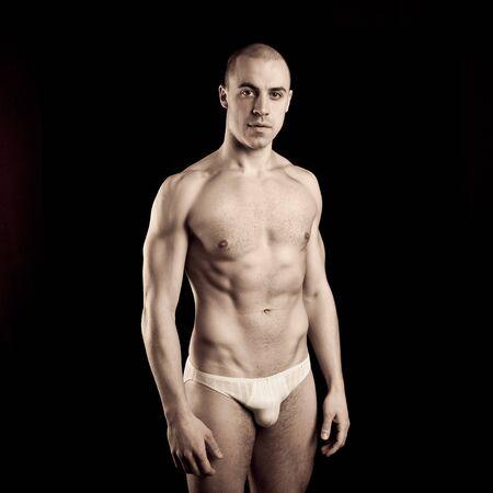 boy underwear: Handsome muscular guy in underwear on black background Stock Photo