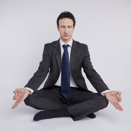 young businessman meditating in yoga lotus pose on white background Stock Photo - 18691879