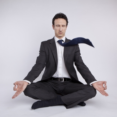 young businessman meditating in yoga lotus pose on white background Stock Photo - 18691877