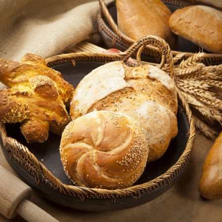 bakery products: assortment of fresh baked bread on wood table Stock Photo