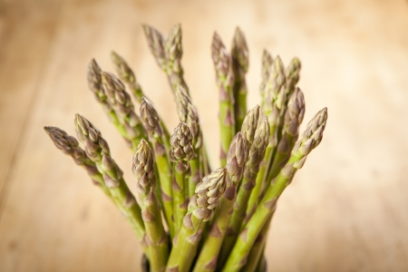 Bunch of fresh green asparagus on wooden background Stockfoto