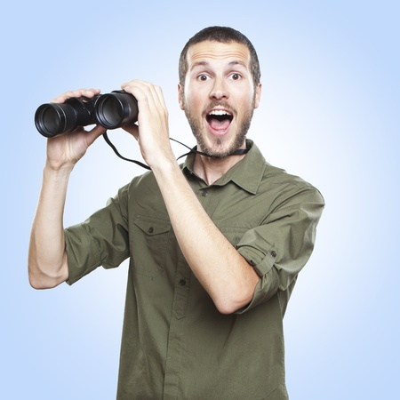 young man looking through binoculars, surprise face expression photo