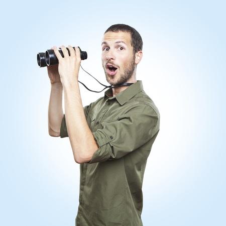cara sorpresa: hombre joven que busca a trav�s de binoculares, expresi�n cara de sorpresa Foto de archivo