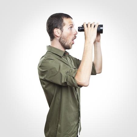 cara sorprendida: hombre joven que busca a través de binoculares, sorprendió a expresión de la cara