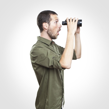 surprised face: young man looking through binoculars, surprise face expression