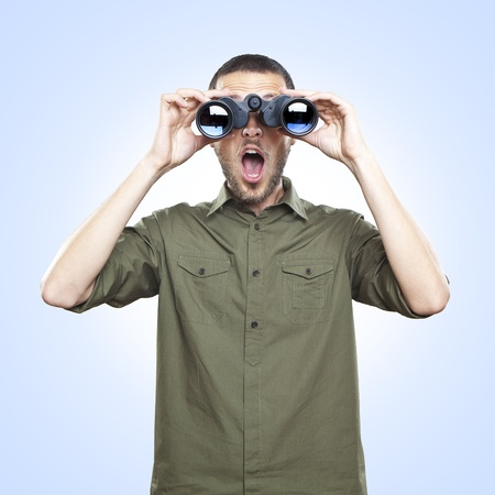 젊은 남자 쌍안경을 통해 찾고, 놀라운 얼굴 식