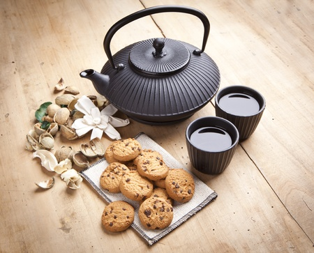 beautiful teapot with chocolate biscuits on wooden table, delicious breakfast photo