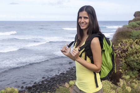 young woman hiking in the nature near the ocean photo