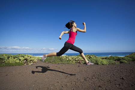 sports activities: atlhlete woman running in nature. Healthy active lifestyle young woman exercising outdoors.