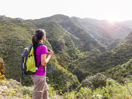 woman hiker with backpack standing on top of a mountain and enjoying stunning valley view photo
