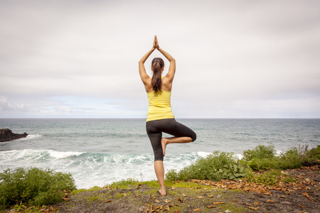 Young woman practicing tree yoga pose near the ocean photo