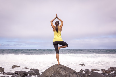 Young woman practicing tree yoga pose near the ocean during sunset photo