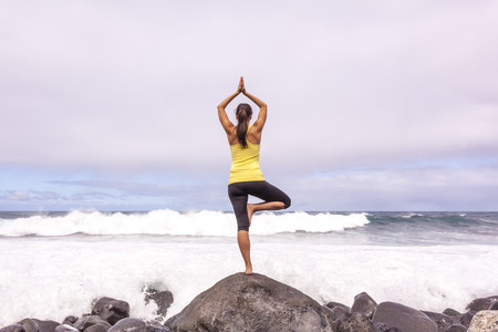 Young woman practicing tree yoga pose near the ocean during sunset Standard-Bild