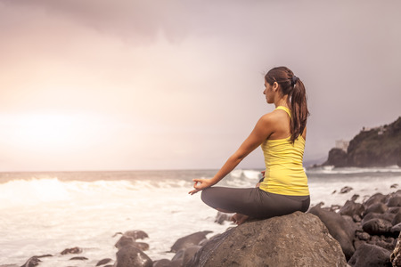 young woman practicing yoga meditation on the beach at sunset, lotus position photo