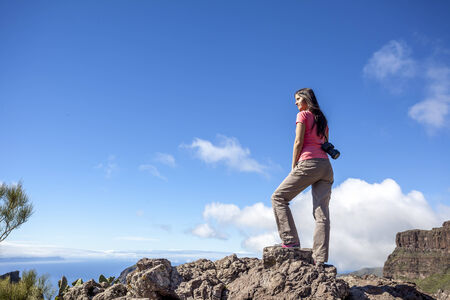 young woman on top of a mountain enjoying the view photo