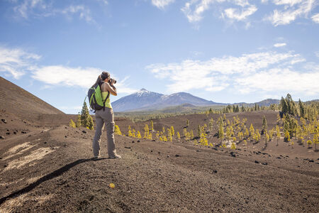 Woman nature Photographer taking pictures outdoors during hiking trip on Teide, Tenerife, Canary Islands. photo