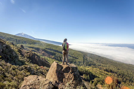 young woman on top of a mountain enjoying the view of volcano teide in tenerife photo